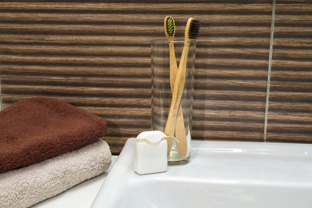 Bamboo toothbrush in glass stand with towel and dental floss in zero waste bathroom