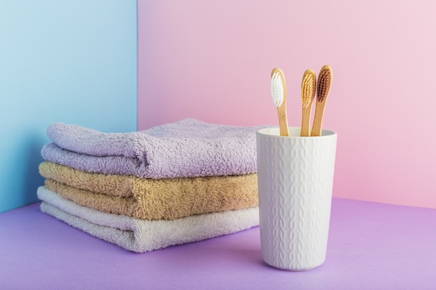 Bamboo toothbrush in glass with towels. dental care hygiene