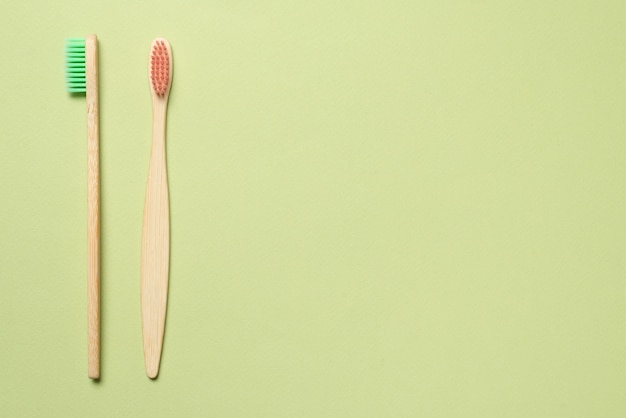 Bamboo toothbrush on a green background. top view.