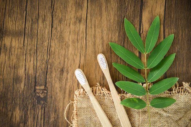 Bamboo toothbrush and green leaf - zero waste bathroom use less plastic concept