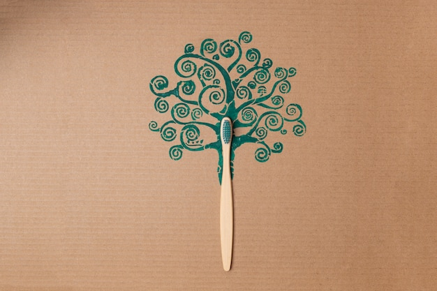 Bamboo toothbrush like tree trunk on cardboard creative concept, plastic free. high quality photo