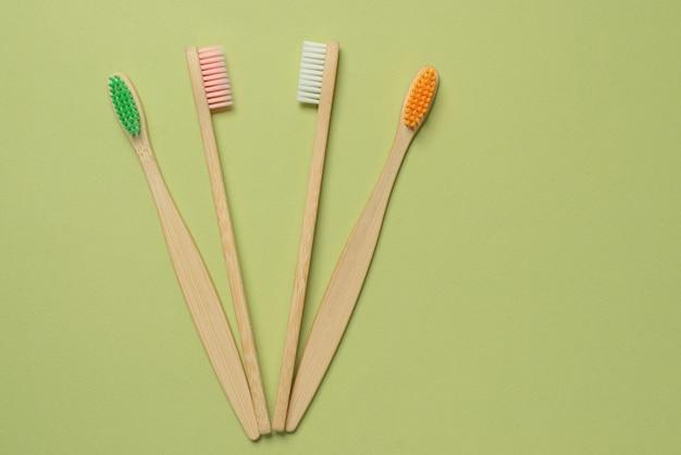 Бамбуковая зубная щетка на зеленом фоне. вид сверху.