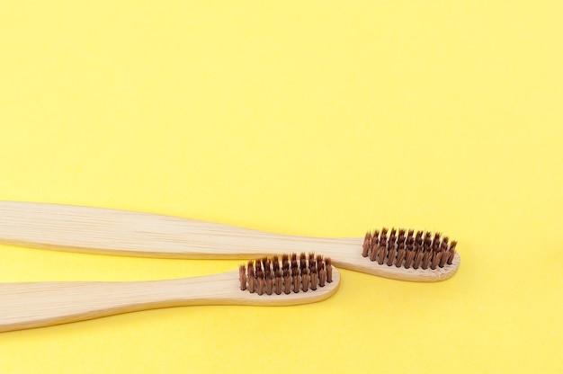 黄色の背景に竹の歯ブラシ。歯の手入れ。エコロジー。コピースペース