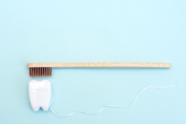 Bamboo toothbrush and white dental floss in the form of a white tooth on a blue background.