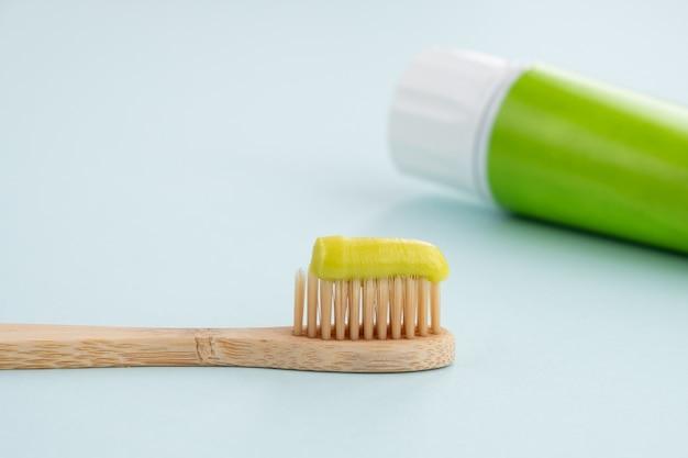 テーブルの上の緑の歯磨き粉と竹の歯ブラシ