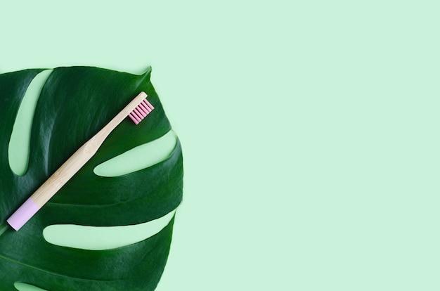 Бамбуковая зубная щетка с натуральной щетиной для ухода за полостью рта на листе монстеры. нулевые отходы