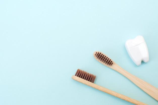 竹の歯ブラシと青い背景の上の白い歯。テキストの場所。