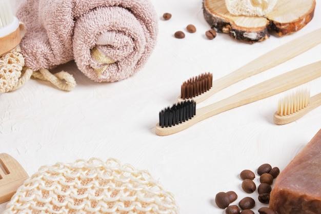 Бамбуковые зубные щетки и аксессуары для ванных комнат из натуральных материалов на бежевой поверхности, образ жизни без отходов