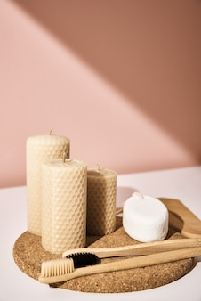 Бамбуковые зубные щетки и свечи на розовом фоне. повторно используйте натуральные продукты