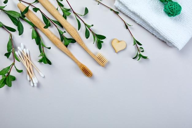 Бамбуковые зубные щетки и ушные палочки и зеленые листья, экологичность, товары личной гигиены без отходов, концепция ухода за зубами