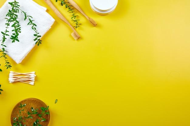 竹製の歯ブラシとタオル付きイヤースティック、黄色い紙の壁に緑の葉、環境にやさしい、廃棄物ゼロの個人衛生製品、歯科治療のコンセプト