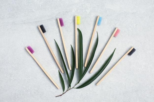 Бамбуковые зубные щетки и зеленые листья на светлом каменном столе. концепция безотходного ухода за собой. без пластика, органические