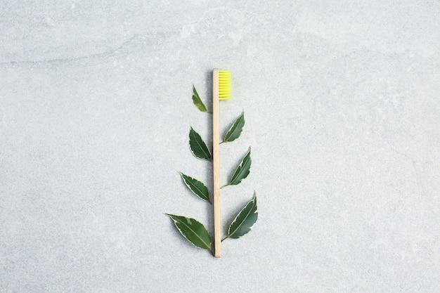 Бамбуковые зубные щетки и зеленые листья на каменном столе