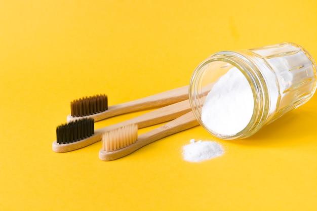 Бамбуковые зубные щетки и банка с содой на желтом фоне, копией пространства, экологической концепции образа жизни