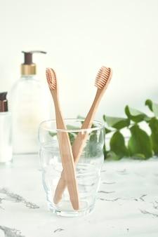 Бамбуковые зубные щетки экологически чистые в стакане с копией пространства на мраморно-белом фоне. ноль отходов. бесплатный пластик.