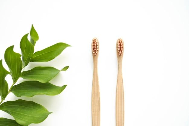 Бамбуковые зубные щетки экологически чистые с копией пространства на белом фоне. ноль отходов. бесплатный пластик. вид сверху.