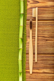 Bamboo toothbrushes, bamboo branch on wooden background. flat lay copy space. natural bath products. biodegradable natural bamboo toothbrush. eco friendly, zero waste, dental care plastic free concept