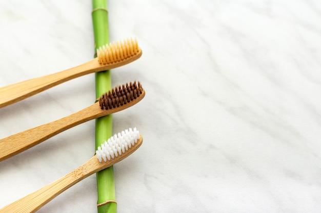 白い大理石の背景に竹の歯ブラシ、竹の植物。平置き。天然バス製品。生分解性天然竹歯ブラシ。環境にやさしい、廃棄物ゼロ、デンタルケア プラスチックフリーのコンセプト。