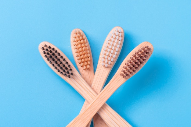 Bamboo toothbrushes on blue background. eco friendly daily oral hygiene, teeth care and health. cleaning products for mouth. dental care concept