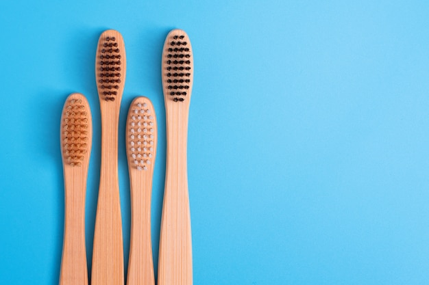 Bamboo toothbrushes on blue background. eco friendly daily oral hygiene, teeth care and health. cleaning products for mouth. dental care concept.