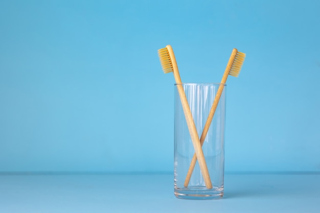 Bamboo toothbrushes on a blue background in a glass ecofriendly personal care products for people