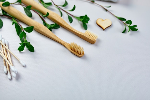 Bamboo toothbrushes and ear sticks, and green leaves on grey paper background
