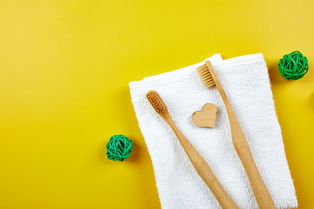 Bamboo toothbrushes and ear sticks, and green leaves on yellow paper wall, eco-friendly, zero waste personal hygiene products, dental care concept