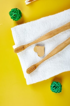 Bamboo toothbrushes and ear sticks with towel, and green leaves, eco-friendly, zero waste personal hygiene products, dental care concept