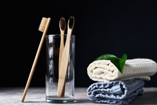 Bamboo toothbrushes in glass and bathroom towels on a dark background