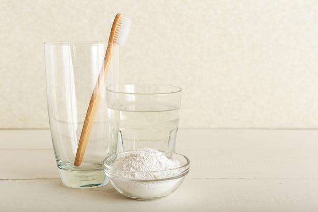 竹の歯ブラシ、水のガラス、白い背景の上の歯磨き粉の歯の粉。生分解性の天然竹歯ブラシ。環境にやさしい、ゼロウェイスト、デンタルケアプラスチックフリーのコンセプト。毎朝の日課。