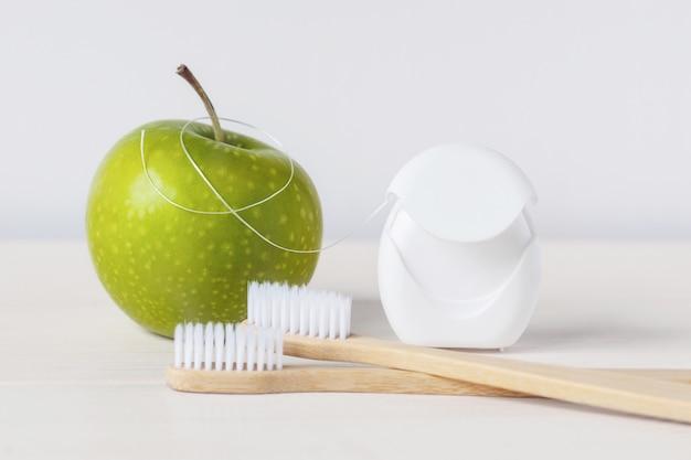 Бамбуковые зубные щетки, зеленое яблоко и зубная нить на белом фоне - уход за зубами для сохранения здоровья зубов