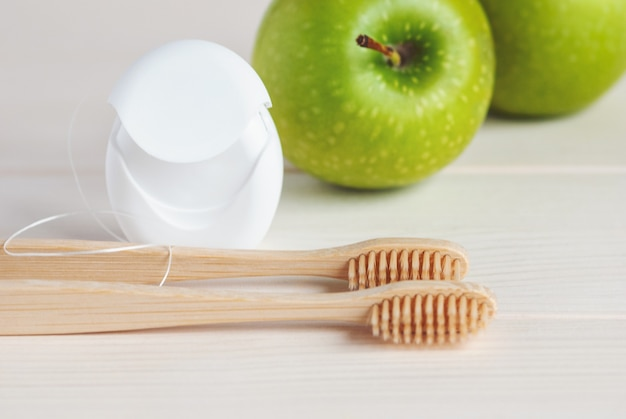 Bamboo toothbrushes, green apples and dental floss, closeup