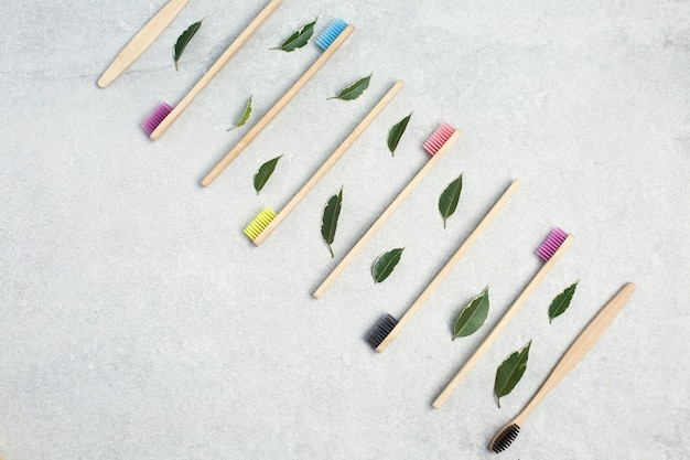 Bamboo toothbrushes and green leafs on light stone table. zero waste concept for self-care . plastic-free, organic