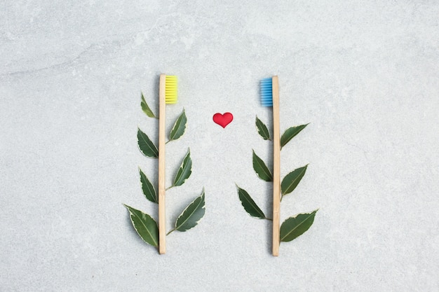 Bamboo toothbrushes, green leafs and red heart on light stone table. zero waste concept for self-care . plastic-free, organic