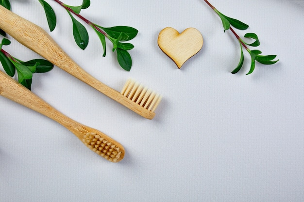 Bamboo toothbrushes, and green leaves on grey paper background