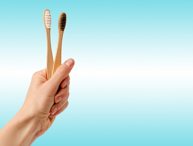 Bamboo toothbrushes in hand on blue space. banner, dental care concept.