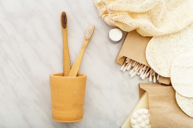 Bamboo toothbrushes in hand made clay glass, soap cotton swabs wooden sticks