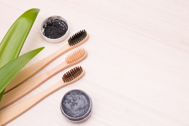 Bamboo toothbrushes and homemade charcoal toothpaste on a wooden table