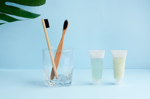 Бамбуковые зубные щетки в стакане и листе монстеры с копией пространства