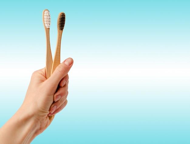 Бамбуковые зубные щетки в руке на синем пространстве. баннер, концепция стоматологической помощи.