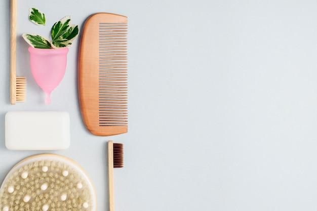 Бамбуковые зубные щетки, менструальная чашка, расческа для волос, мыло на сером фоне с копией пространства. ноль отходов концепция, повторное использование.