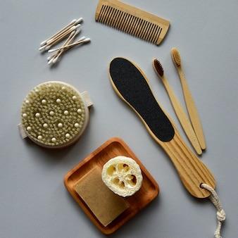 竹の歯ブラシ、木の板に天然石鹸とバスヘチマ、木製のドライマッサージブラシ、その他の環境に優しいボディケア製品