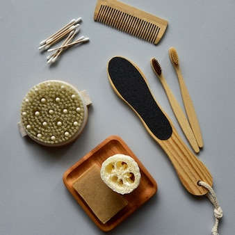 Bamboo toothbrushes, natural soap and bath loofah on a wooden plate, wooden dry massage brush and other eco-friendly body care products
