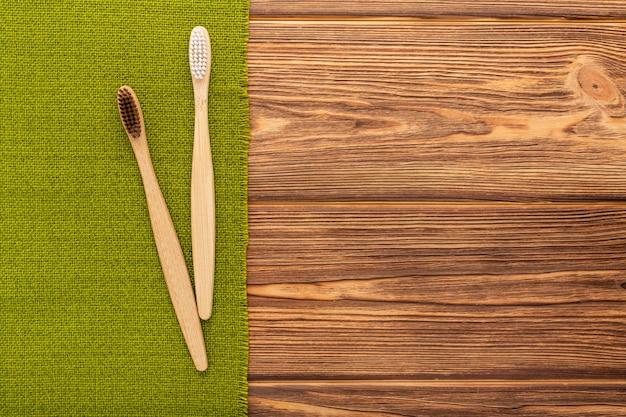 木製の背景に緑のタオルの上に竹の歯ブラシを平らに置き、コピースペースの自然なバス製品を...