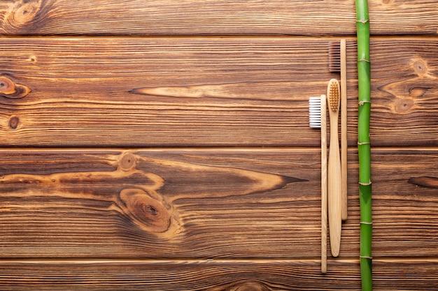 나무 배경에 있는 대나무 칫솔은 평평한 복사 공간 천연 목욕 에코 제품