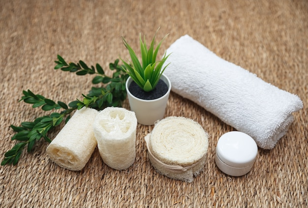 Bamboo toothbrushes, white towel, luffa sponge, handmade organic soap with green aloe. eco friendly bathroom and hygiene accessories.