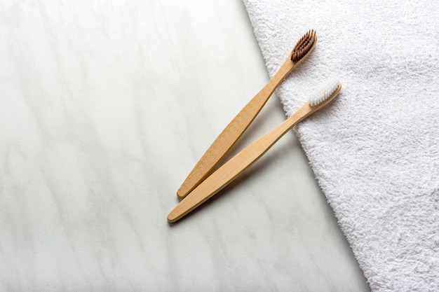 Bamboo toothbrushes on white towel on marble background. flat lay copy space. natural bath products. biodegradable natural bamboo toothbrush. eco friendly, zero waste, dental care plastic free concept