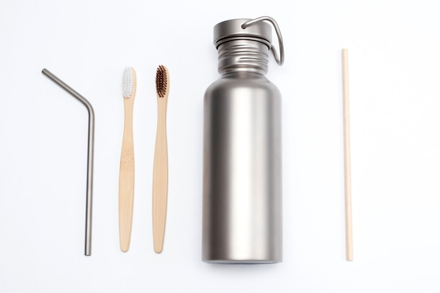 Bamboo toothbrushes with titanium hydration bottle and reusable stainless steel straws. zero waste concept.