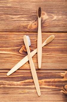 Bamboo toothbrushes on wooden background. flat lay with copy space. natural bath products. biodegradable natural bamboo toothbrush. eco friendly, zero waste, dental care plastic free concept.