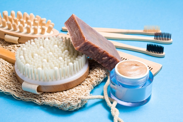 Bamboo toothbrushes, wooden comb, knitted washcloth, natural homemade scrub in a jar and homemade soap and dry massage brush on a blue surface